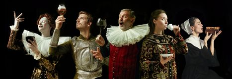 Medieval men and women as a royalty person. In vintage clothing drinking wine and coffee and eating on dark background. Concept of comparison of eras, modernity stock images