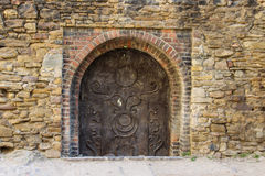 Medieval Metal Door. A decorated medieval metal door in a stone and brick wall with a sun motif in the old center of Medias, Romania stock photo