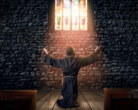 Medieval monk kneeling and praying in church stock photography