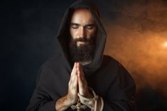 Medieval monk praying with closed eyes stock photos