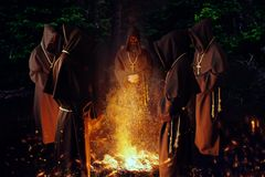 Medieval monks praying against a fire in the night royalty free stock photo