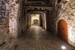 Medieval narrow street leading under arches. Small middle-age street in Tallinn, Estonia Stock Image