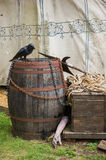 Medieval objects. Crow on the old wooden barrel and other medieval objects in front of the knigt tent Stock Photo