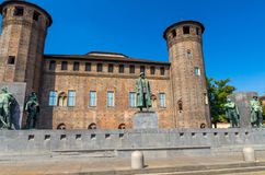 Medieval old Acaja Castle with brick towers and Monumento Emanuele Filiberto Duca d`Aosta on Castle Square Piazza Castello in his. Torical centre of Turin Torino royalty free stock image