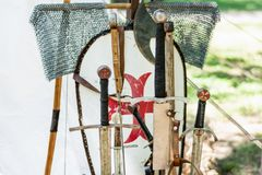 A medieval old group of swords and knights equipment. Very old medieval old group of swords and knights equipment. Close up of handles sword and blurred shield stock photography