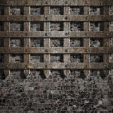 Medieval old rusty metal lattice on stone wall Royalty Free Stock Image