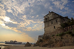 Medieval Ouranoupoli Tower with pilgrims ferry boat, Chalkidiki, Greece Royalty Free Stock Images