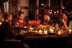 Medieval people eat and drink in ancient  castle kitchen interior. Royalty Free Stock Photo