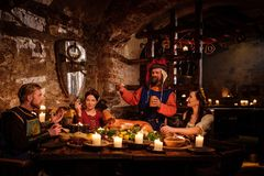 Medieval people eat and drink in ancient castle kitchen interior. royalty free stock image