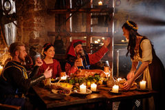 Medieval people eat and drink in ancient castle kitchen interior.  royalty free stock photography