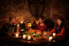 Medieval people eat and drink in ancient castle kitchen interior Royalty Free Stock Images