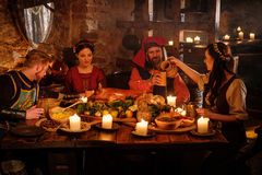 Medieval people eat and drink in ancient castle kitchen interior.  stock image