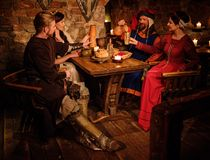 Medieval people eat and drink in ancient  castle tavern. Stock Image
