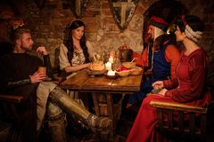 Medieval people eat and drink in ancient  castle tavern. Royalty Free Stock Images