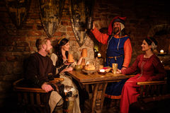 Medieval people eat and drink in ancient castle tavern.  stock photography