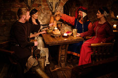 Medieval people eat and drink in ancient castle tavern Royalty Free Stock Images