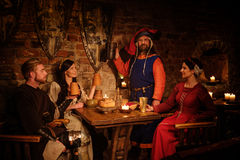 Medieval people eat and drink in ancient castle tavern.  royalty free stock photography