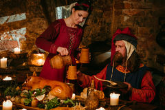 Medieval people eat and drink in castle tavern. Royalty Free Stock Photo
