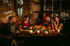 Medieval people eat and drink in castle tavern. stock photography