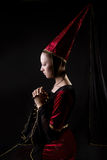 Medieval portrait of woman in historical costume. Stylized medieval style portrait of a beautiful woman in historical costume. low key. Looking down. Stage make stock image