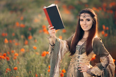 Medieval Reading a Book in a Magical Field of Poppies Royalty Free Stock Photos
