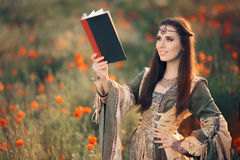 Medieval Reading a Book in a Magical Field of Poppies Royalty Free Stock Photography