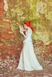 Medieval redhead princess with hairstyle in corset. Queen with hairdo against stone wall. Fairytale doll. Medieval princess with. Mirror in palace. Fairy queen royalty free stock images
