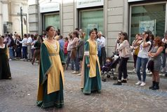 Medieval reenactment parade. Color image. Mortara, Italy - September 24, 2017: a couple of youg women, dressed in Reinassance costumes, parade through the Royalty Free Stock Image