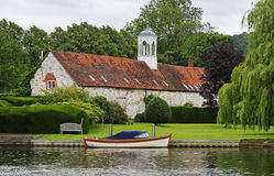 Medieval Riverside Building with moored boat Stock Image