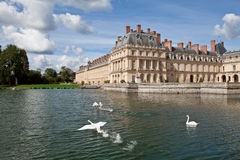 Medieval royal castle Fontainbleau near Paris. Medieval landmark royal hunting castle Fontainbleau near Paris in France and lake with white swans Stock Photo