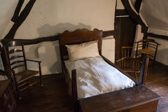 Medieval rustic bedroom. Interior of a medieval rustic bedroom with wooden bed, case and chairs royalty free stock image