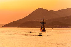 Medieval sailing ship in sunset. Old medieval sailing ship in sunset on the open sea with hills in the distance Stock Images