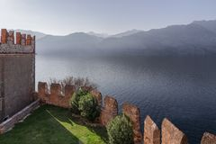 The medieval Scaliger Castle Il Castello Scaligero di Malcesine and the view of the Alps in the fog from Lake Garda in Malcesine stock image