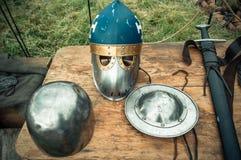 Medieval scene. Medieval knight attributes are helmet, chain mail, shield buckler, sword, halberd. Reconstruction of medieval life. Medieval scene. Medieval Stock Image