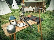 Medieval scene. Medieval knight attributes are helmet, chain mail, shield buckler, sword, halberd. Reconstruction of medieval life. Medieval scene. Medieval Stock Photography