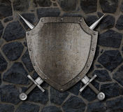 Medieval shield and crossed swords on wall stock photo