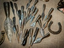 Medieval small arms. Steel ancient arrowheads, horseshoes, spear Stock Photography