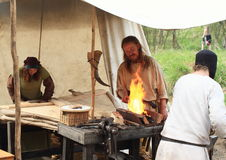 Medieval smith. In forge with two big bellows and two helpmates Stock Images