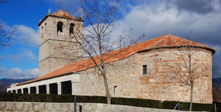Medieval Spanish church. Exterior of medieval church with bell tower; blue sky and cloudscape background, Guadarrama, Spain Stock Photos