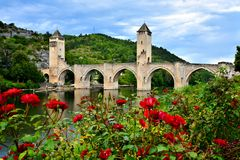 Medieval stone bridge at Cahors, France with red roses. Medieval stone bridge at Cahors, France with red rose flowers Stock Photography