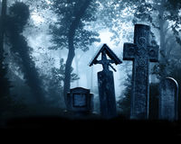 Medieval stone crosses and tombstones, cemetery in misty forest Royalty Free Stock Photos
