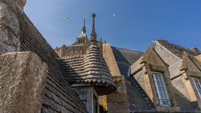 Medieval stone house in normandy. Cupolas and roofs of Mount San Michele, ancient abbey by the tidal floods several times a day and that served in medieval times royalty free stock image