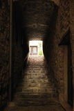 Medieval stone stairs in the dark, there is bright light outt of the tunnel Stock Photo