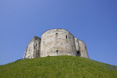 Medieval stone tower. Landmark medieval stone tower on a grassy motte or mound in the centre of the historic city of york known as cliffords tower Stock Photo