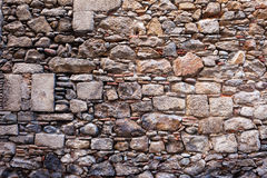 Medieval Stone Wall Background. Or texture made with different sizes of rough cut stones and some bricks between, Old Town of Girona in Spain royalty free stock photography