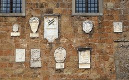 Medieval stone wall with bas-reliefs, Italy. Medieval stone wall with bas-reliefs in tuscany town Sovana, Grosseto, Tuscany, Italy stock images