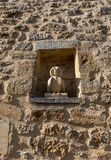 Medieval stone wall with a small statue of owl in Domme, Dordogne. France stock photo