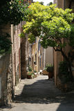 Medieval Street. Very narrow street in medieval French village of Mougins.  No people, no vehicles.  Street slopes downhill and is flanked by old stone buildings Stock Images