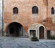 Medieval street arch under an ancient brick wall of a building facade in the town of Cividale del Friuli. Now in italy Royalty Free Stock Photography