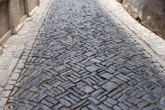 Ancient corridor with medieval cobbles, Thuringia, Germany. Medieval street with cobblestones and grungy walls, Thuringia, Germany royalty free stock photo